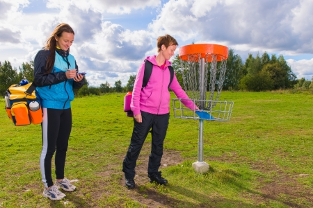 disc golf: Women beside the basket during the disc golf game