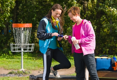 disc golf: Women checks accounting after game, horizon format Stock Photo