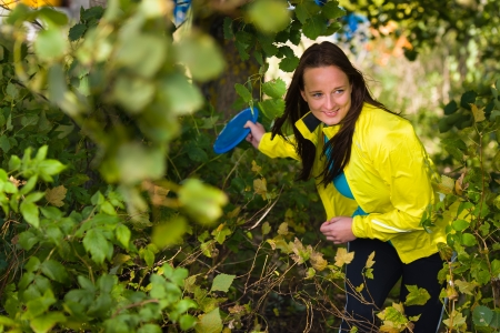 Woman get ready to throw a disc out the bush, horizon format Stock Photo