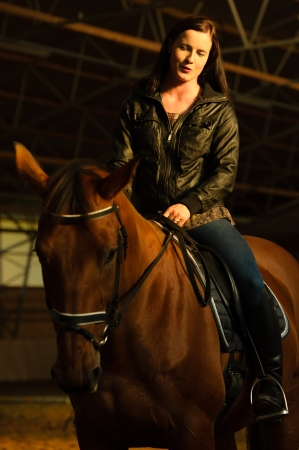 Woman and horse in indoor arena, woman watch the horse, vertical format photo
