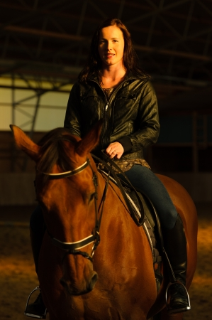 Woman and horse in indoor arena, woman looks toward camera, vertical format photo