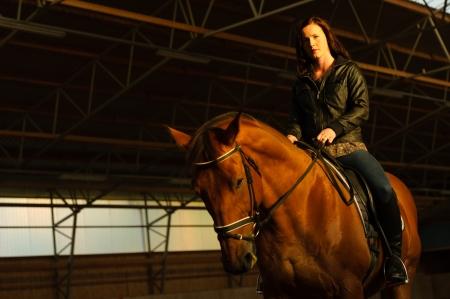 Woman and horse in indoor arena, woman looks toward camera, horizon format photo