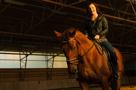 Smiling woman with a horse in indoor arena, woman looks toward camera, horizon format photo