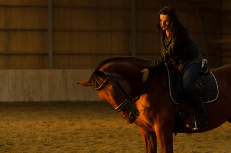 Woman taps the horse in indoor arena, woman looks toward the horse, horizon format