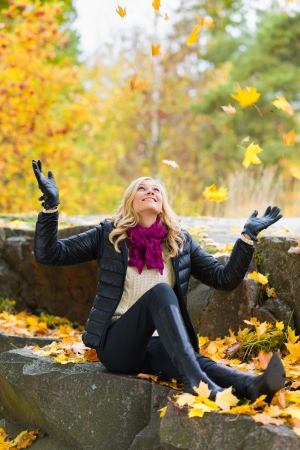 Beautiful girl and falling leaves, autumn color