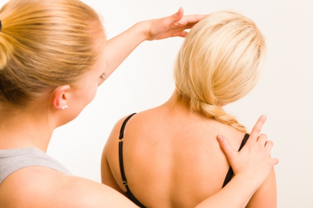 Masseur examining a womans body, white wall on background photo