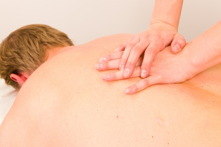 Professional masseur doing massage of male back photo