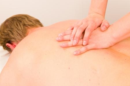 Professional masseur doing massage of male back