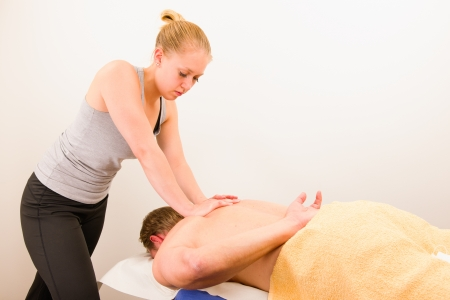 Professional masseur doing massage of male back
