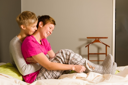 Lesbian couple on a bedroom in the morning photo