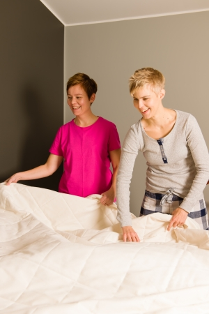Lesbian couple make the bed in the morning, vertical format photo