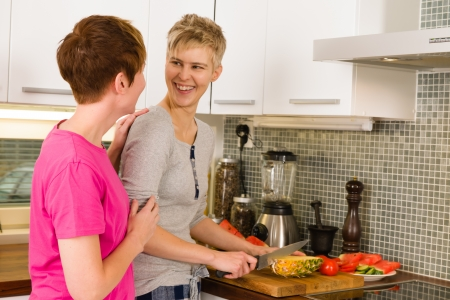 Happy lesbian couple making a breakfast in the kitchen, horizon format