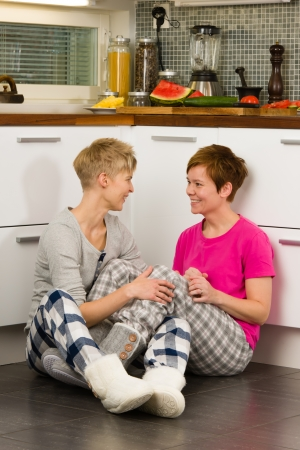 Lesbian couple sits on the kitchen floor together photo