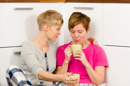 Lesbian couple drinking coffee on a kitchen floor, horizon format photo