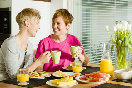 Happy lesbian couple sits on the breakfast table photo