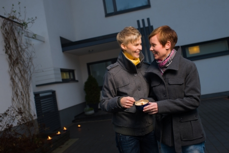 Happy lesbian couple light a candle on front yard of the house photo