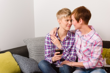 Happy lesbian couple having a good time together on the living room photo