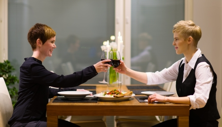 Happy lesbian couple sits on a dinner table and having good time together photo
