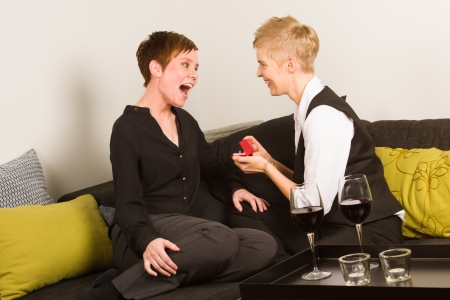 Lesbian proposing her girlfriend with a engagement ring on the living room photo