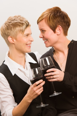Two happy lesbians and a glass of red wine, vertical format photo