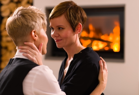 A portrait of a lesbian couple in love, fireplace on background, horizon format photo