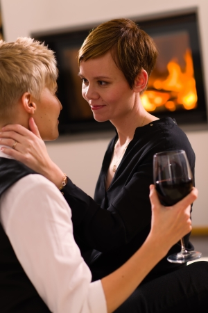 A portrait of a lesbian couple in love, fireplace on background, vertical format photo