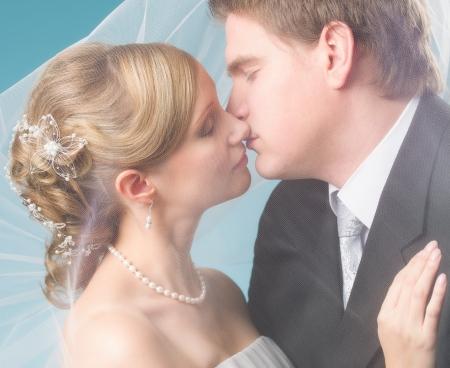 bridal couple: Bridal couple kissing under a veil, blue background