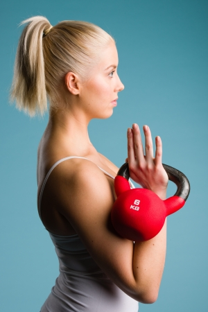 Fitness girl holds a kettlebell in rack position, blue background photo
