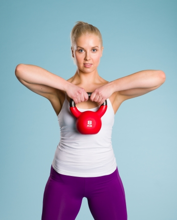 Fitness girl use a kettlebell, blue background Stock Photo