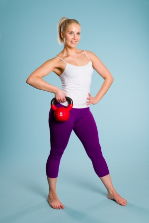 Fitness girl poses with a kettlebell, blue background photo