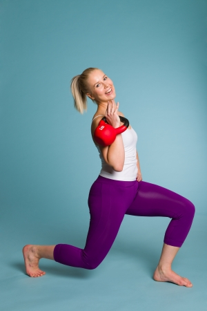 Fitness girl on squat position with a kettlebell photo