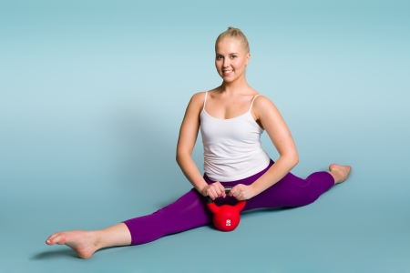 Fitness girl poses with a kettlebell, blue background, horizon format photo