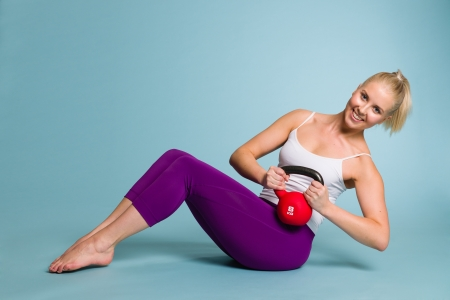 Fitness girl in Russian twist position with a kettlebell photo