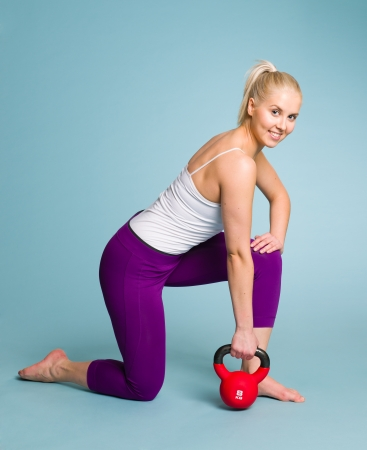 Fitness girl in one arm row position with a kettlebell photo