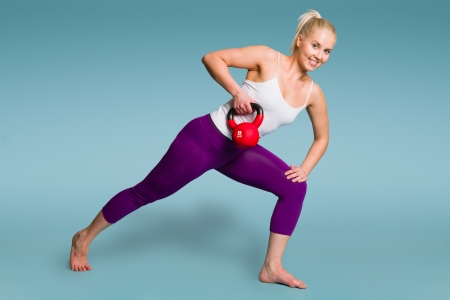 Fitness girl in one arm row position with a kettlebell