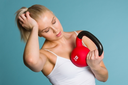 fatigued: Fitness girl being tired and feeling fatigued, she holds a kettlebell