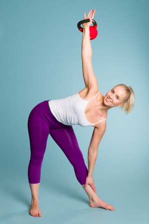 Fitness girl in windmill position with a kettlebell photo