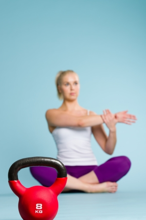 Fitness girl stretching and focus on the kettlebell front of her photo