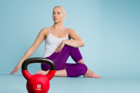 Fitness girl stretching and focus on the kettlebell front of her, horizon format photo