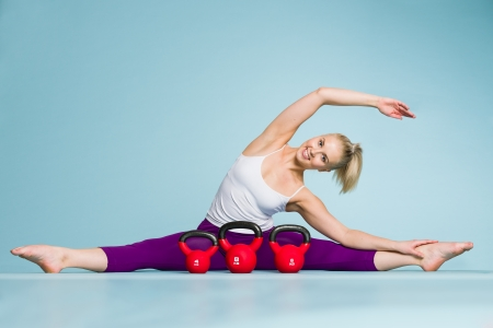 Fitness girl stretching and the kettlebells front of her, vertical format photo