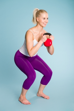 Fitness girl in half squat position with a kettlebell photo