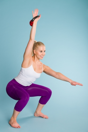Fitness girl in squat position with a kettlebell photo