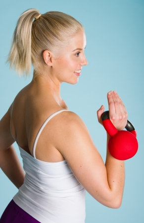 Fitness girl use a kettlebell, blue background, vertical format photo