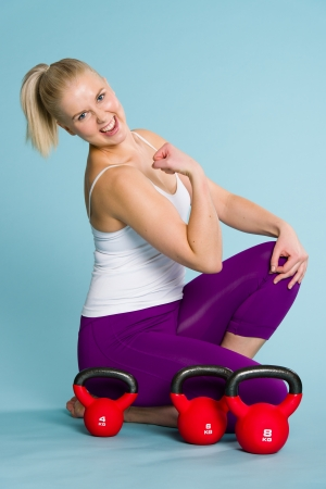 Smiling fitness girl showing her arm, the kettlebells on background photo