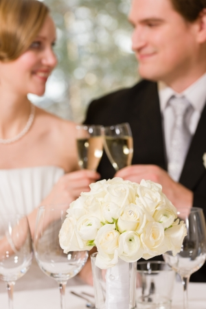 Bridal bouquet, bride and groom toasting champagne on background photo