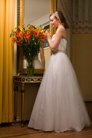 body image: Beautiful bride sniffs flowers, full body image