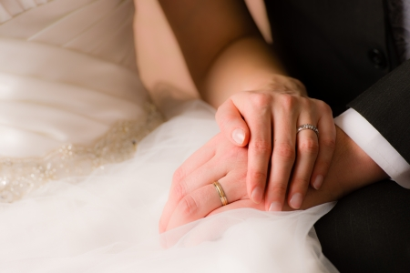 Closeup of a bride and groom holding hands photo