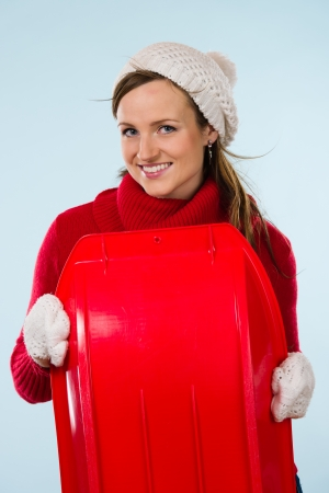 wooly: Beautiful young sporty woman with sled wearing a wooly outfit, vertical format