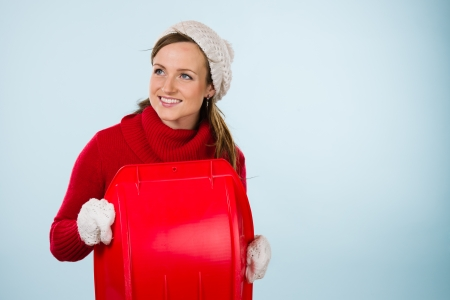 Beautiful young sporty woman with sled wearing a wooly outfit, horizon format photo