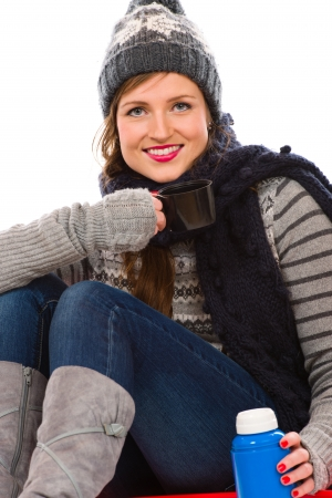 Beautiful young woman with thermos bottle wearing wooly outfit, white background photo